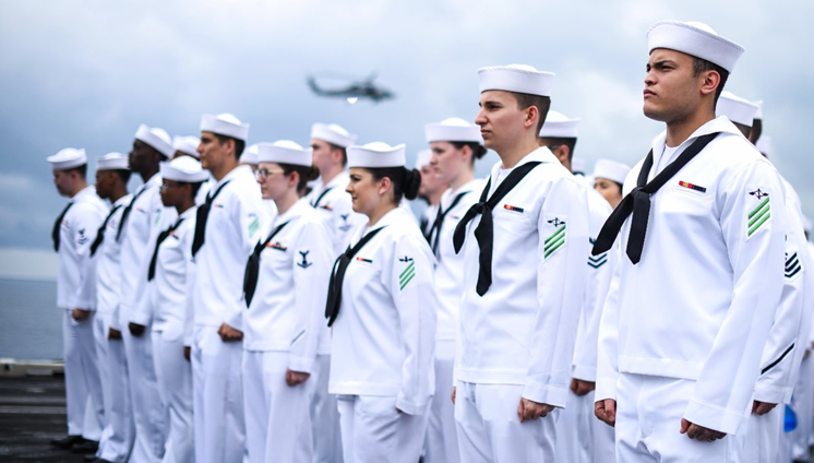 Navy personnel standing at attention on a ship