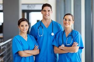 Three nurses in blue scrubs