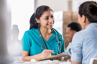 Cherokee scrubs Attentive young doctor talks with female patient