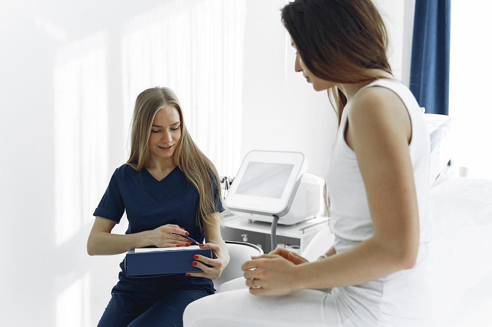 Nurse in Dark Blue Scrub Checking on Female Patient