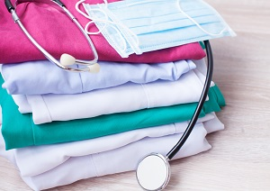 Pile of Folded Scrubs with a Stethoscope and Mask on Top