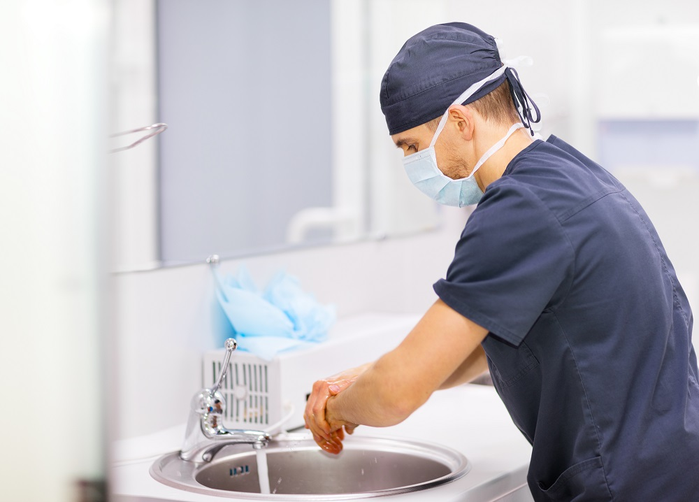 Doctor in scrubs washing hands